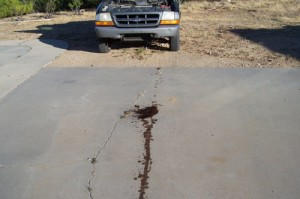 Oil leak on a concrete driveway before applying DE-OIL-IT to clean it and completely remove it.