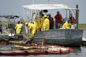 Workers check on oil skimmers containing oil from the Deepwater Horizon spill in Bay Jimmy near Venice, La., June 11, 2010. Photo credit AP.