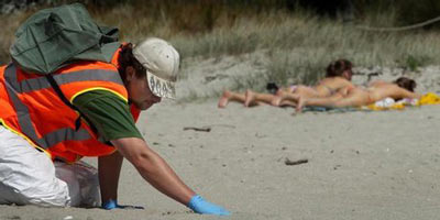 Sunbathers can enjoy Mt Maunganui beach, but the arduous hands-and-knees job of clearing fuel oil washed ashore from the Rena will drag on ... and more pollution could come if the ship breaks up.
