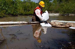 Wading In A cleanup worker lays oil absorbent materials into the Yellowstone River, July 6, 2011.