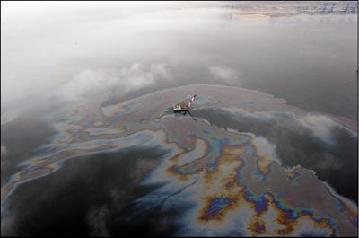 An aerial photo, released by China's Xinhua news agency on July 17, 2010, shows an oil slick floating off the coast of Dalian, China. Efforts were under way to contain and clean up a large oil slick after pipeline explosions at the northeastern Chinese port sent greasy black plumes into the ocean, state media reported. (AP Photo/Xinhua, Tian Jingyue)