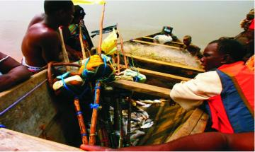 A boat with fishermen and dead fish off the coast of Bonga which is affected by the Shell oil spill.
