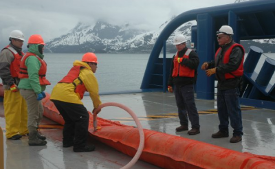 Workers unroll inflatable boom and fill it before casting it off into Valdez waters during oil spill response training for Shell.
