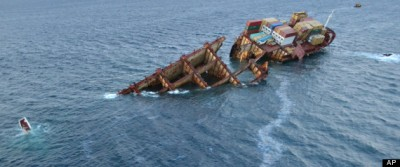 In this photo taken Monday, Jan. 16, 2012, provided by Maritime New Zealand, an oil sheen flows from the cargo ship Rena which is almost completely submerged on a reef near Tauranga, New Zealand. (AP Photo/Maritime New Zealand)